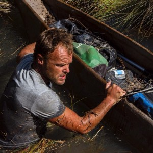 The expedition camp manager, Pieter Hugo wading the mokoro through a deep channel